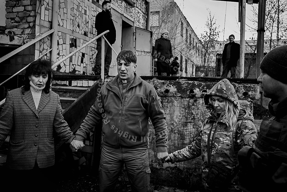 Oleg Tkachemko, 47, (centre) a Chaplin from the 'Good News Church' in Slovakisk, is praying with soldiers and volunteers after meeting them in the town of Maryinka, near the frontline in eastern Ukraine.