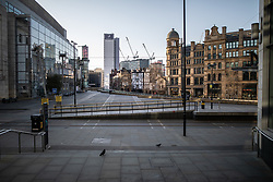 © Licensed to London News Pictures. 26/03/2020. Manchester, UK. Exchange Square lies empty during the evening rush hour . Manchester City Centre lies nearly empty during a sunny spring afternoon . The British government has imposed a lockdown on all but essential activities and instructed people to reduce social contact as part of quarantine measures to prevent the spread of Coronavirus ( COVID-19 ) . Photo credit: Joel Goodman/LNP