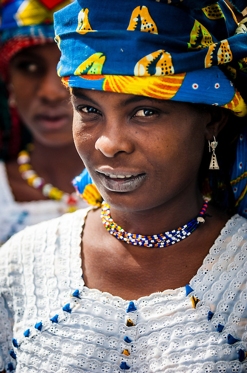 Portrait of a Peuhl girl dressed in her finest clothes in northern Burkina Faso. The Fulani or Peuhl are nomadic herdsmen of the Sahel region of West Africa. The darker lower lip from indigo staining, facial tattoos and silver jewellery are traditional markings of Fulani women.