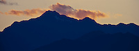 Mount Jupiter in the Olympic Mountains stands silhouetted against a twilight sky as seen from the Kitsap Peninsula in Puget Sound, Washington state, USA pan