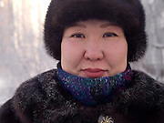 Street portrait of a Yakutian woman protected with the traditional fur cap and warm clothing against the extrem cold. Yakutsk is a city in the Russian Far East, located about 4 degrees (450 km) below the Arctic Circle. It is the capital of the Sakha (Yakutia) Republic (formerly the Yakut Autonomous Soviet Socialist Republic), Russia and a major port on the Lena River. Yakutsk is one of the coldest cities on earth, with winter temperatures averaging -40.9 degrees Celsius.