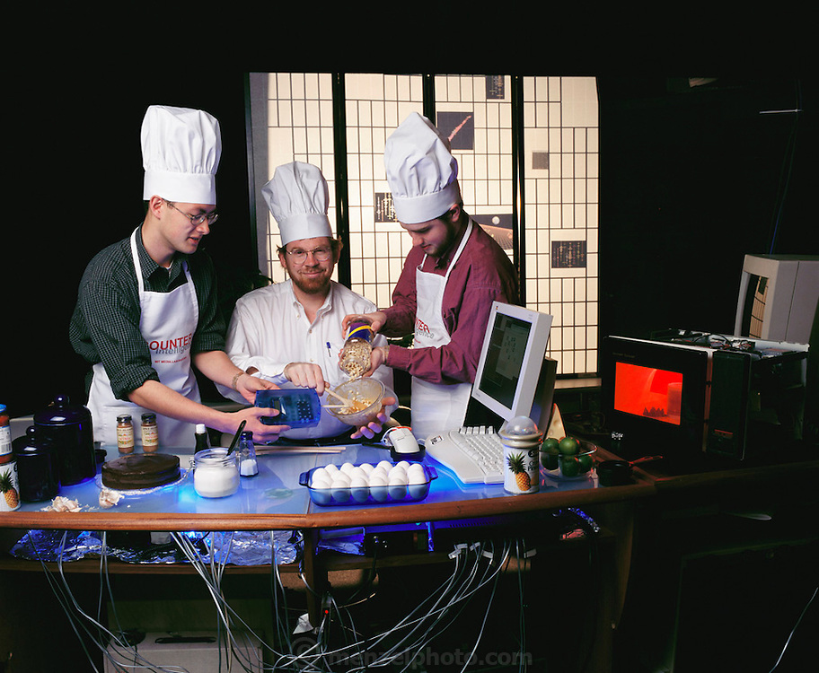 Future kitchen. Professor Mike Hawley (middle) and colleagues from the Massachusetts Institute of Technology (MIT), USA, in the 'kitchen of the future' prototype. Here, one of Hawley's colleagues (at left) is holding a 'digital nose' device. This analyses smells from the bowl's contents. It then tells the user (via the computer at center right) how fresh the food is and suggests further ingredients. This is all part of MIT's Counter Intelligence project which includes using computers in food preparation and laying the table, as well as the inclusion of computer-simulated dinner guests. MODEL RELEASED. (1999)