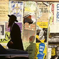 Israel, Jerusalem, Orthodox Jewish man walks past brightly colored posters lining sidewalk in Mea Shearim