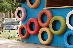 Painted tires and blue wall, Heidelberg Project, Detroit, Michigan.  The Heidelberg Project is a grass roots project started by artist Tyree Guyton that uses art to help revitalize the embattled neighborhood.  Each year, over 275,000 people visit the project .  For more information, go to www.heidelberg.org