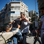August 10, 2012 - Aleppo, Syria: A group of men gives assistance to a man, injured minutes earlier by heavy shelling from the Syrian Army against a bakery in the residential area of Tariq Al-Bab in central Aleppo. At least 12 people have died and more the 20 got injured during the attack...The Syrian Army have in the past week increased their attacks on residential neighborhoods where Free Syria Army rebel fights have their positions in Syria's commercial capital, Aleppo. (Paulo Nunes dos Santos/Polaris)