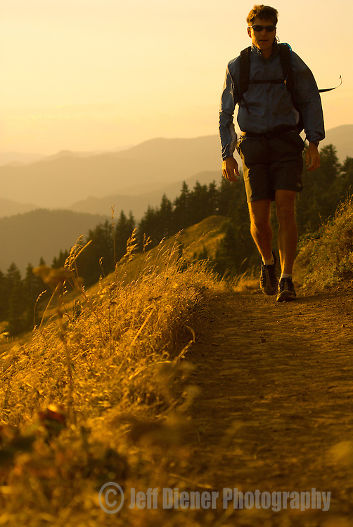 A young man hikes along the Dog Mountain Trail in the Columbia River Gorge, Washington.