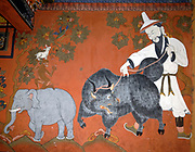 Painting illustrating the ancient Tibetan Buddhist tale of the Four Friends or Harmonious Brothers on a wall. The four friends are an elephant, a monkey, a hare (sometimes a rabbit)  and a partridge (sometimes a peacock or grouse). The fable relates both to the status due to age and cooperation.  The four friends establish their ages and hence rank by recounting their earliest recollections of a banyan tree. By cooperating the four firends can reach fruit high in a fruit tree.   There is also a picture of a bearded man with a white hat and robes holding an agressive looking yak on a leash.  Paro Dzong, Druk Yul,  Bhutan. 10 November 2007