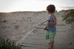 Side view of a boy playing on the beach during sunset, Lit-et-Mixe, Aquitaine, France