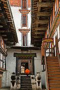 Monk running up stairs inside Jakar Dzong, Bumthang