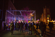 People enjoying the 'Submergence' installation by Squid Soup as part of Cheriton Light Festival 2018 on Cheriton High Street, Folkestone, Kent, United Kingdom.