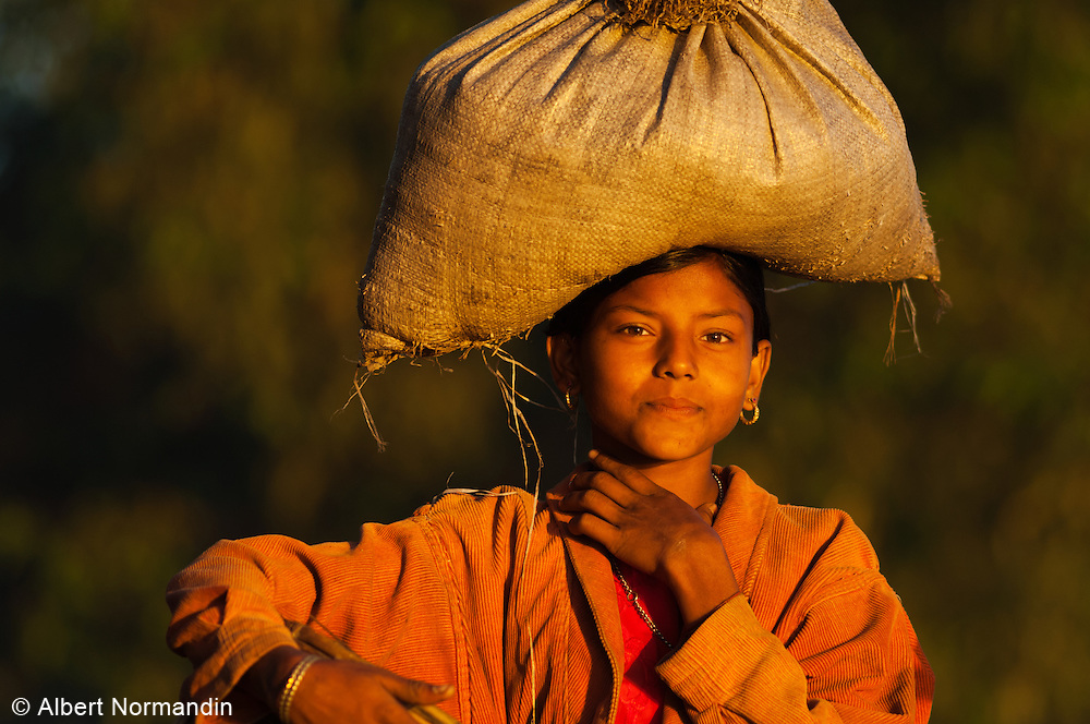 Young girl with sack on her head and sunrise light