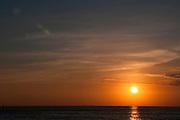 A horizontal image of the sun at sunset in Waikiki.