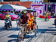 29 OCTOBER 2018 - PHRA PRADAENG, SAMUT PRAKAN, THAILAND: A Buddhist monk in a cyclo rickshaw, sometimes called a samlor (Thai for three wheels) near the Chao Phraya River in Phra Pradaeng. The Chao Phraya River is the lifeline of central Thailand. Water from the river, and its tributaries, provides domestic and agricultural water to homes and farms. It's also a major commercial artery with large ocean going freighters going up to Bangkok's Khlong Toey port.         PHOTO BY JACK KURTZ