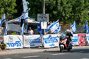 A handful of Likud supporters stand in front of the anti corruption Protesters on an ongoing sit down protest are protesting the alleged crimes of corruption and mis management of the state by Prime Minister Benjamin (Bibi) Netanyahu in front of the official residence in Balfour street, West Jerusalem, Israel Photographed on 22 July 2020.