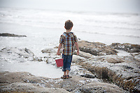 A young boy with visits the beach at Lincoln City, Oregon with his red bucket.