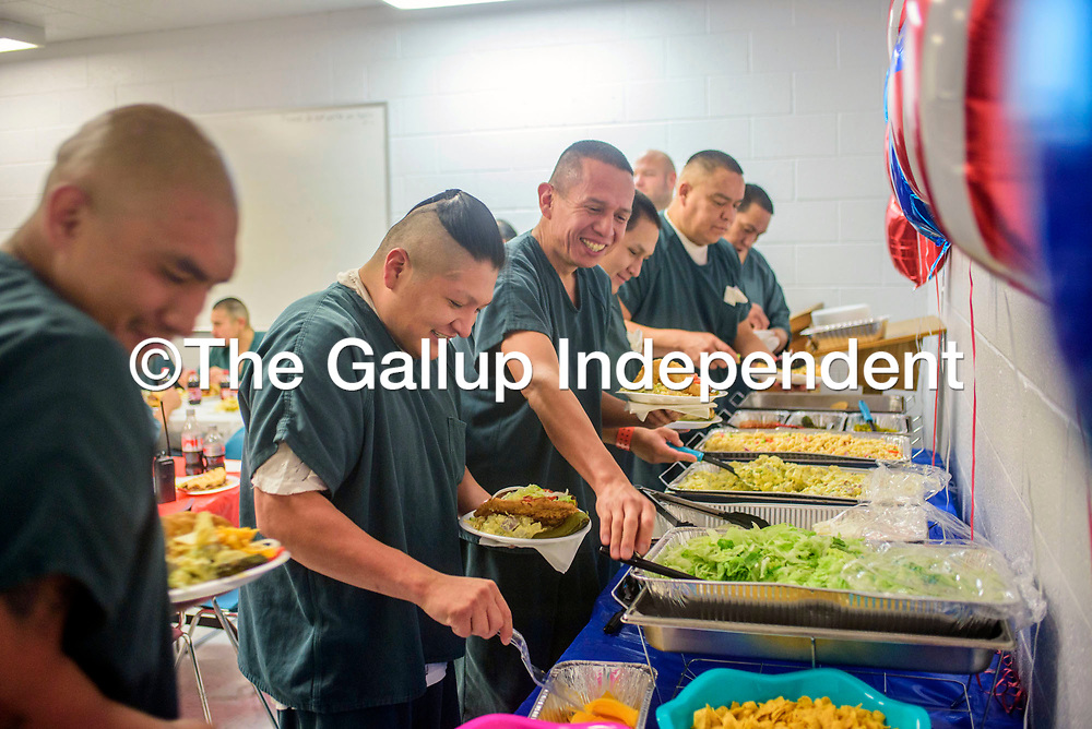 Participants in the McKinley County Adult Detention Center Treatment Program line up for food during a graduation luncheon at the jail in Gallup Wednesday.