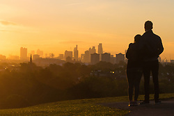 Primrose Hill, London, October 4th 2016. A couple on Primrose Hill admire the vivid colours as dawn breaks across London's skyline.