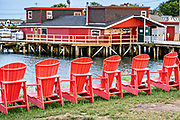 Red Adirondack chairs lined up outside Cook's Lobster Wharf on Orrs Island, Maine.