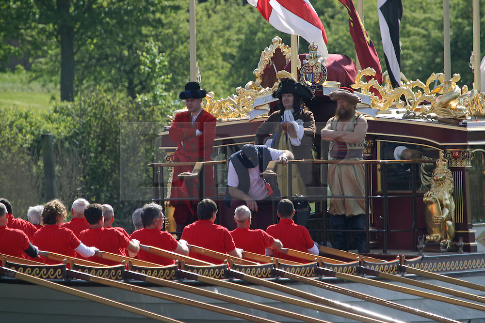 """© Licensed to London News Pictures. 18/04/2014. The Queen's Row Barge Gloriana on the Thames at Hampton Court in Good Friday's glorious sunshine. It was the first engagement of 2014 for the popular row barge and she was rowed to Hampton Court Palace with """"King George I"""" on board for the palace's Glorious Georges season .  Credit : Rob Powell/LNP"""