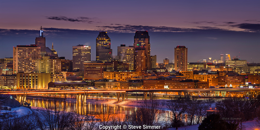"""Downtown St. Paul gives off a beautiful glow. This view from Mounds Park is the only place where you can see the downtowns of St. Paul and Minneapolis in the same frame. And one of the rare occasions when Minneapolis takes a back seat to St. Paul! The First Bank """"1"""" is ice blue this week to recognize the state high school hockey tournaments occurring in St. Paul. This panorama is a composite of three photos"""