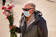 09 MARCH 2021 - DES MOINES, IOWA: A man carries flowers to a flower filled coffin during a memorial service for the 5,574 Iowans killed by COVID-19 in the one year since the pandemic started. Each flower represented an Iowan killed in the pandemic. The first three cases of the Coronavirus (SARS-CoV-2), all Iowans who had traveled to Egypt on a cruise, were reported to the Iowa Department of Public Health on March 8, 2020. The first fatality in Iowa was reported on March 25, 2020.    PHOTO BY JACK KURTZ