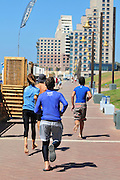 Israel, Haifa, Dado Beach, group of people jog on beach