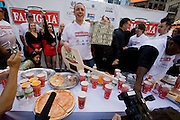 Competitive eater Joey Chestnut holds a plastic briefcase with $5,000 after winning the Famous Famiglia world championship pizza eating contest in New York City's Times Square. (Joey Chestnut is included in the book What I Eat: Around the World in 80 Diets.) He won the $5,000 first prize after eating 45 slices of cheese pizza in 10 minutes.  Each slice weighed 109 grams (3.84 ounces) and contained 260 calories. In ten minutes Joey consumed 10.81 pounds (4.9 kilograms) of pizza and drank a gallon of water. The pizza contained 11,700 calories.