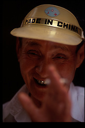 """BEIJING, CHINA - An elderly man sells souvenirs to tourists and sports a hat that reads """" Made In China """". (Photo © Jock Fistick)"""