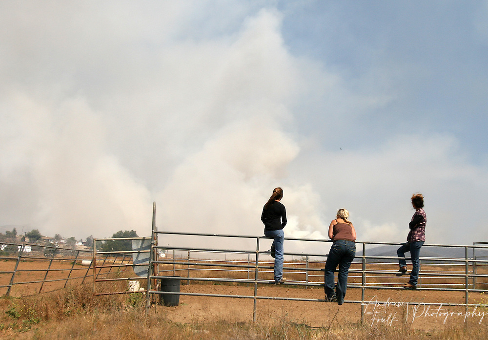 /Andrew Foulk/ For the Californian/.French Valley residents sit on the bars of a horse pen and  watch the plume of smoke from a fire that started at around 2pm in the area just North of Keller Road and South of Scott Road. The Fire consumed an estimated 200 acres and caused the closure of Scott, and Winchester Roads.