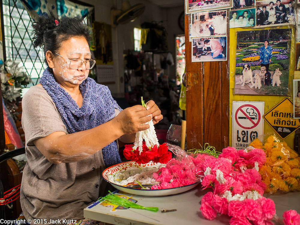 11 FEBRUARY 2015 - BANGKOK, THAILAND:  A woman makes and sells flower garlands for people going to either the Chinese shrine next door or to  Wat Kalayanamitr, a large Buddhist temple across the street from the shrine. The neighborhood around Santa Cruz Catholic church is known for the Thai adaptation of Portuguese cakes baked in the neighborhood. Several hundred Siamese (Thai) Buddhists converted to Catholicism in the 1770s. Some of the families started baking the cakes. When the Siamese Empire in Ayutthaya was sacked by the Burmese, the Portuguese and Thai Catholics fled to Thonburi, in what is now Bangkok. The Portuguese established a Catholic church near the new Siamese capital. There are still a large number of Thai Catholics living in the neighborhood around the church.     PHOTO BY JACK KURTZ