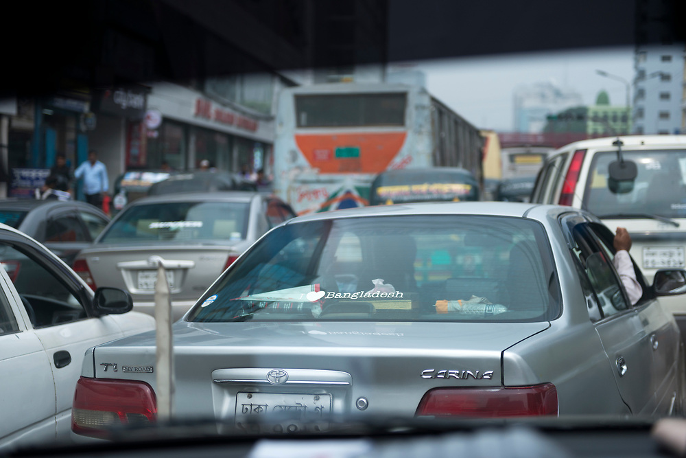 """View through the windshield of a car in heavy traffic, looking at the decal on another car that says """"I love Bangladesh,"""" in Dhaka, Bangladesh"""