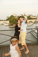 couple taking photos on the Pont des Arts, Paris