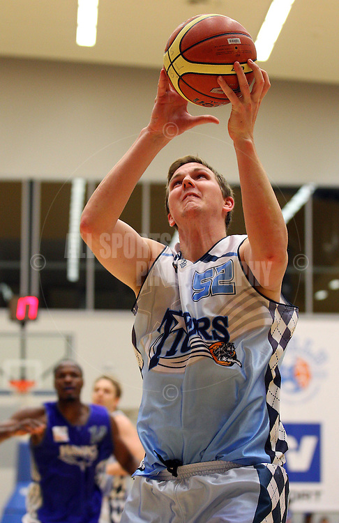 PERTH, AUSTRALIA - JULY 16: Travis Moore of the Tigers pulls down a rebound during the week 18 SBL game between the Perry Lakes Hawks and the Willetton TIgers at The State Basketball Center on July 16, 2011 in Perth, Australia.  (Photo by Paul Kane/Allsports Photography)