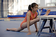 A Chinese girl stretches her legs before a workout during an afternoon training session of the Beijing Gymnastic team.