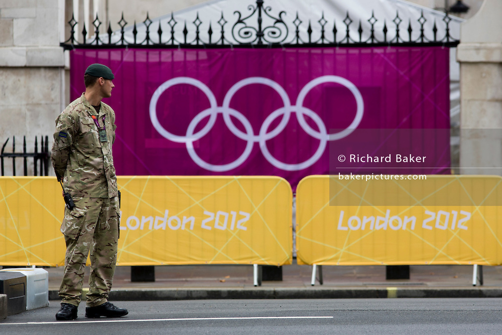 A soldier of the British army stand guarding the entrance to the volleyball venue in central London next to the IOC rings logo on day 4 of the London 2012 Olsecure.  A total of 18,000 defence personel were called upon to make the Games secure following the failure by security contractor G4S to provide enough private guards. The extra personnel have been drafted in amid continuing fears that the private security contractor's handling of the £284m contract remains a risk to the Games.