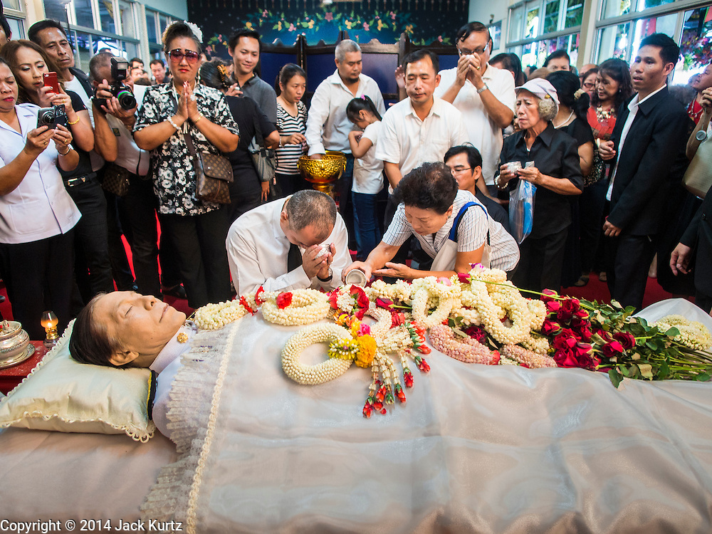12 OCTOBER 2104 - BANG BUA THONG, NONTHABURI, THAILAND: Red Shirt leader NATTAWUT SAIKUA (left) and other Red Shirt supporters pray at the funeral rites for Apiwan Wiriyachai at Wat Bang Phai in Bang Bua Thong, a Bangkok suburb, Sunday. Apiwan was a prominent Red Shirt leader, member of the Pheu Thai Party of former Prime Minister Yingluck Shinawatra, and a member of the Thai parliament. The military government that deposed the elected government in May, 2014, charged Apiwan with Lese Majeste for allegedly insulting the Thai Monarchy. Rather than face the charges, Apiwan fled Thailand to the Philippines. He died of a lung infection in the Philippines on Oct. 6. The military government gave his family permission to bring him back to Thailand for the funeral. He will be cremated later in October. The first day of the funeral rites Sunday drew tens of thousands of Red Shirts and their supporters, in the first Red Shirt gathering since the coup.    PHOTO BY JACK KURTZ