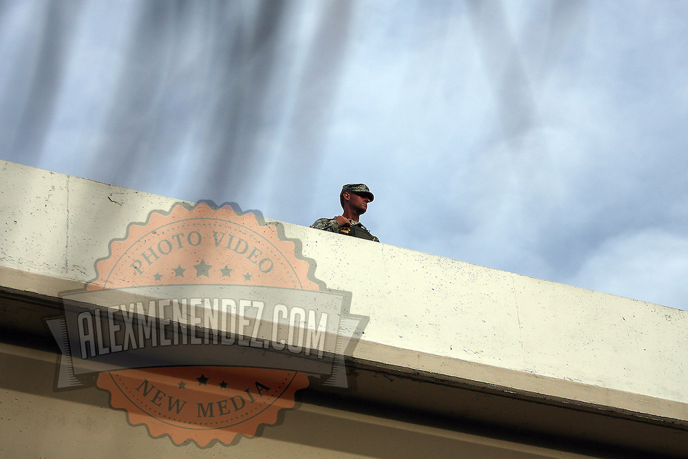 A lone Police officer observes from an overhead highway bridge as protesters carry signs while marching in a parade during the Republican National Convention in Tampa, Fla. on Wednesday, August 29, 2012. (AP Photo/Alex Menendez)