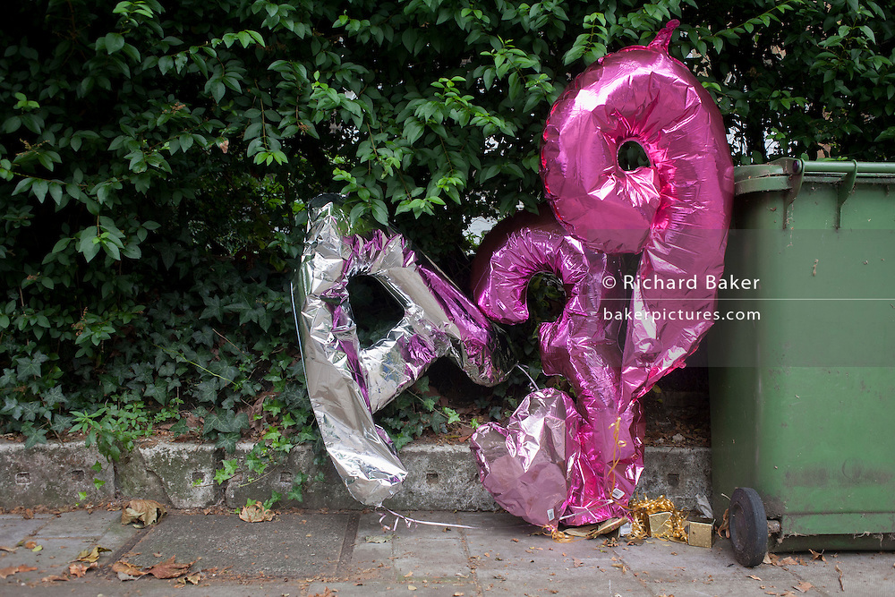 Thirty-ninth birthday balloons abandoned next to bins in Camberwell, south London borough of Southwark.