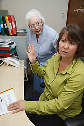 Woman in office trying to work being disturbed by mother.