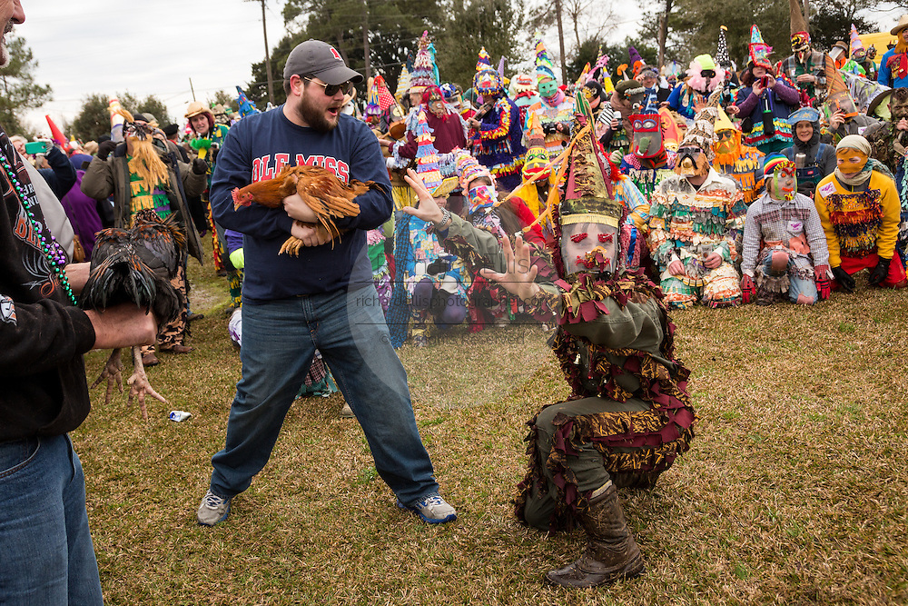 A home owner protects his chicken from costumed revelers during the Faquetigue Courir de Mardi Gras chicken run on Fat Tuesday February 17, 2015 in Eunice, Louisiana. The traditional Cajun Mardi Gras involves costumed revelers competing to catch a live chicken as they move from house to house throughout the rural community.
