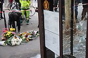 Bullet holes and blood on window panes. Flowers on the street. Cafe Bonne Biere, Rue Fontaine au Roi, near Republique<br /><br />The Day after the terrorist jihadi attacks. Bullet holes and blood, mourning homage and cleaning up. Aftermath of deadly Paris terrorist attacks. Saturday 14th November 2015<br /> <br /> Eight terrorists dead and some 128 people killed at Stade de France, Bataclan concert Hall, Belle Equipe Restaiurant, Rue Fontaine au Roi, Two hundred people have been injured, 80 of them seriously.