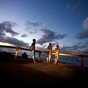 Teen surfers wait for a ride home at dusk after surfing in Noosa Heads, Australia.