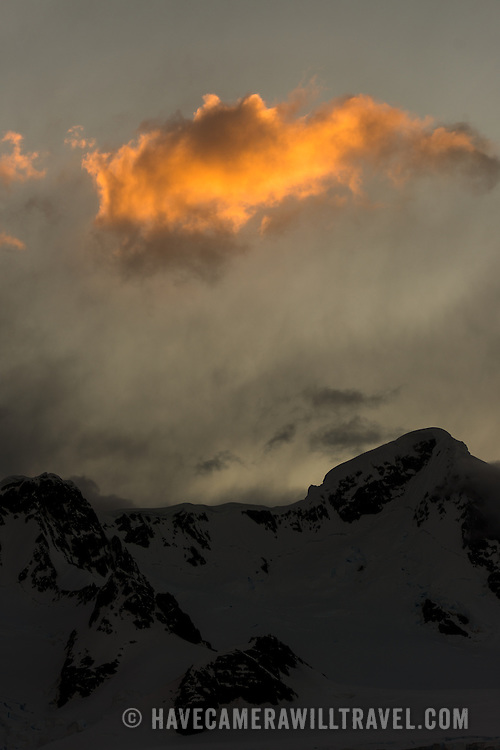 The day's last rays of golden sun catch a cloud above a moutnain range at Paradise Harbor, Antarctica.