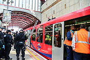 Police officers begin to remove climate change protesters who glued themselves to the roof of a Docklands Light Railway carriage on April 17, 2019 in London,England, United Kingdom.This is the third day of a coordinated protest by the Extinction Rebellion group who are demanding the government decisive action from the UK Government on climate change.