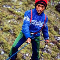 Nuru Jangbu Sherpa (from Pangboche)  learns to rappel at an early mountaineering school for sherpas in the Khumbu region of Nepal, 1980.