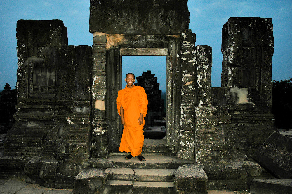 This sunset image of a monk in an ancient ruin of a door is from the hilltop temple in Angkor Wat. The Hill Temple of Phnom Bakheng is one of the most ancient of all the Angkor temples. It is popular as a sunset viewpoint with an average of 3000 people climbing it each day.<br /> <br /> The temple is a Hindu temple in the form of a temple mountain. Dedicated to Shiva, it was built at the end of the 9th century, during the reign of King Yasovarman (889-910 A.D.)<br /> <br /> Constructed more than two centuries before Angkor Wat, Phnom Bakheng was in its day the principal temple of the Angkor region.<br /> <br /> It is well worth the climb to the top!