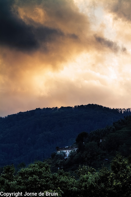 A lonely house in the hills of Tuscany under a sky being lit by the setting sun.