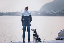 THEMENBILD - eine Frau schaut vom Nordufer des Zeller See auf die Stadt Zell am See, daneben sitzt ein Hund, aufgenommen am 03. Dezember 2020, Zell am See, Österreich // a woman looks from the north shore of the Zeller See at the town Zell am See, next to her is a dog on 2020/12/03, Zell am See, Austria. EXPA Pictures © 2020, PhotoCredit: EXPA/ Stefanie Oberhauser