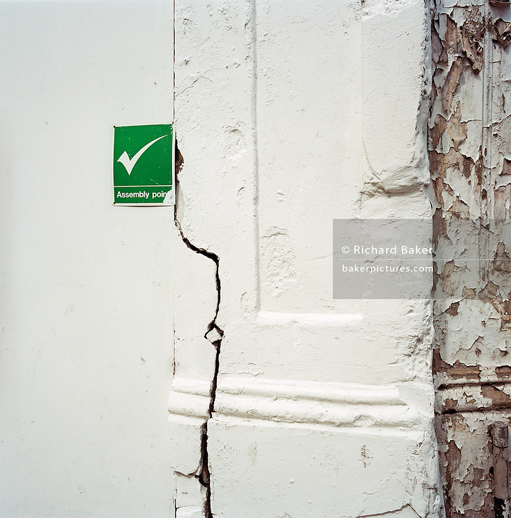 The sign for an Assembly Point is on a white wall, cracked and unsafe near a construction site.