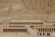 """A few tourists approach the ancient Egyptian Temple of Hatshepsut near the Valley of the Kings, Luxor, Nile Valley, Egypt. The Mortuary Temple of Queen Hatshepsut, the Djeser-Djeseru, is located beneath cliffs at Deir el Bahari (""""the Northern Monastery""""). The mortuary temple is dedicated to the sun god Amon-Ra and is considered one of the """"incomparable monuments of ancient Egypt."""" The temple was the site of the massacre of 62 people, mostly tourists, by Islamists on 17 November 1997."""